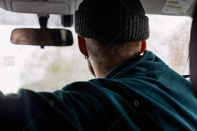 Side view of man wearing knit hat traveling in car
