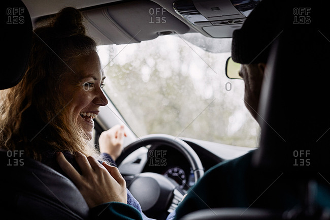 Cheerful female talking with male friend while traveling in car