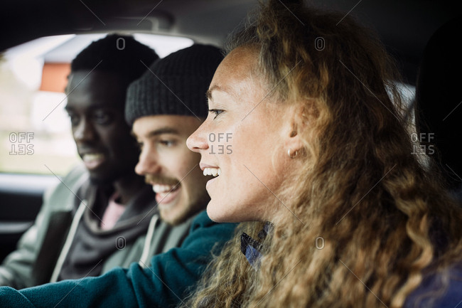 Friends looking away while enjoying in car