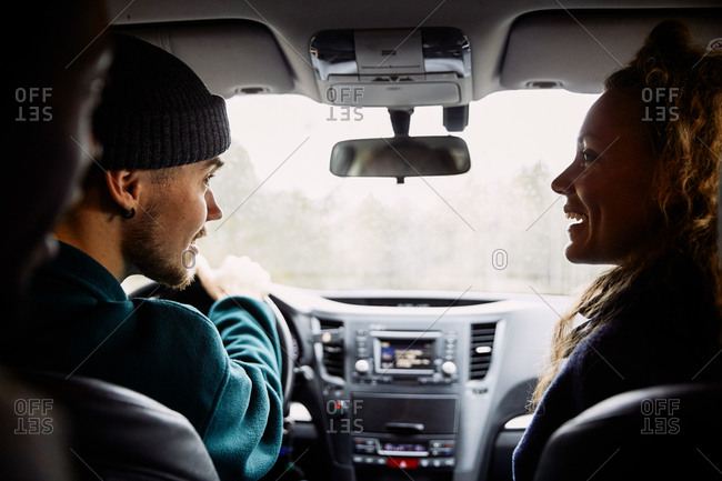 Male and female friends talking while traveling in car