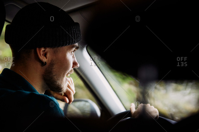 Smiling young man wearing knit hat while driving car