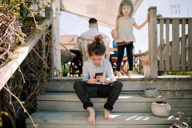 Girl looking at sister using mobile phone while sitting on steps in patio