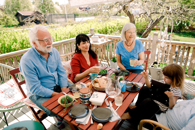 Multi-generational family enjoying food at table in patio