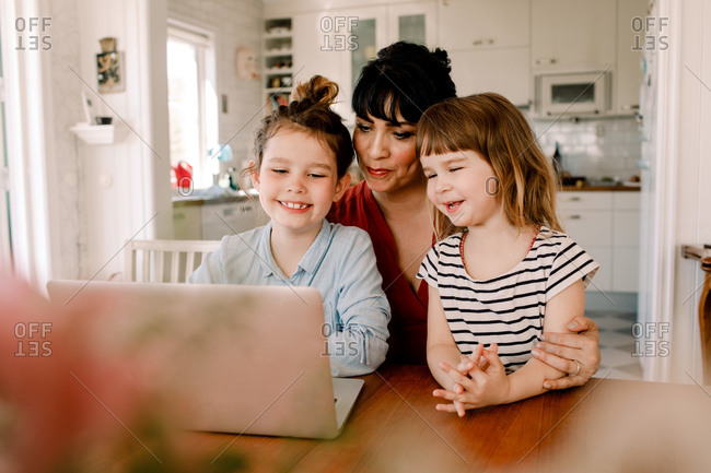 Mother and daughters looking at laptop while sitting in living room