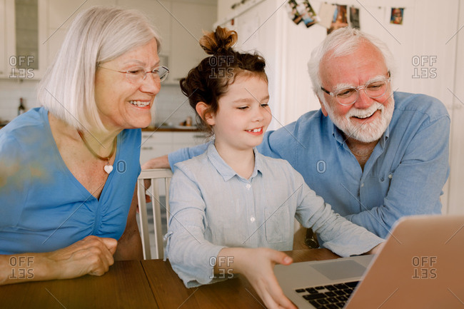 Girl showing laptop to smiling grandparents at home