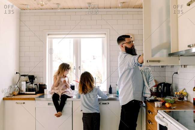 Girl looking at working sister while father doing chores in kitchen