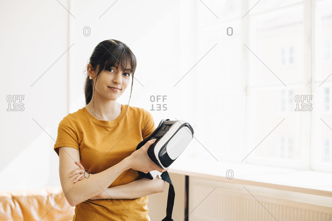 Portrait of female entrepreneur holding virtual reality simulator while standing by window