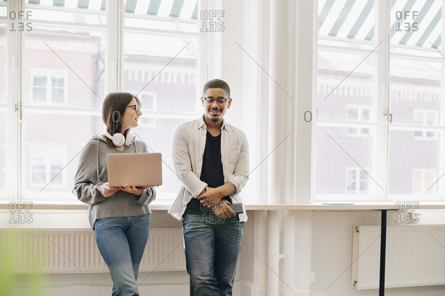 Smiling computer programmers talking while standing by desk in office