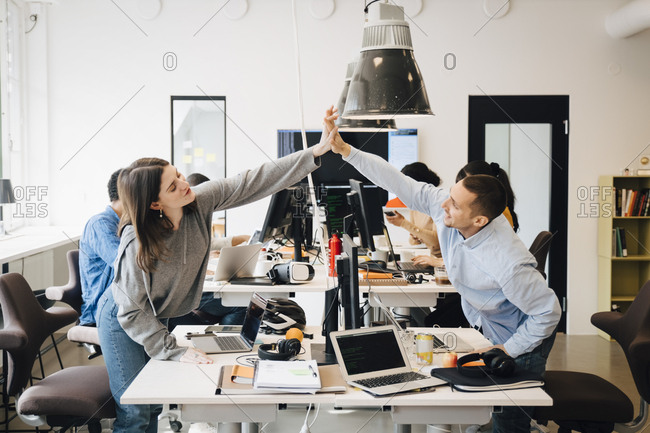 Happy male and female computer programmers doing high-five over computer at desk in creative office