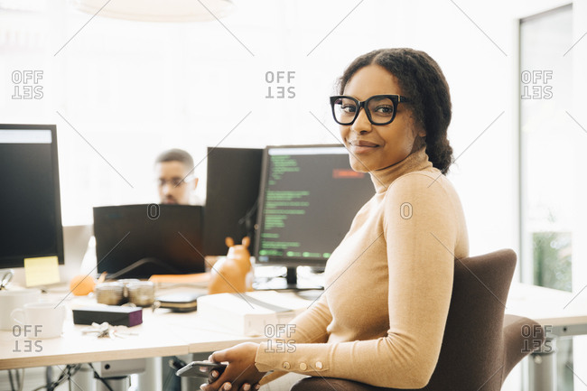 Portrait of female programmer sitting by desk with colleague in background at creative office
