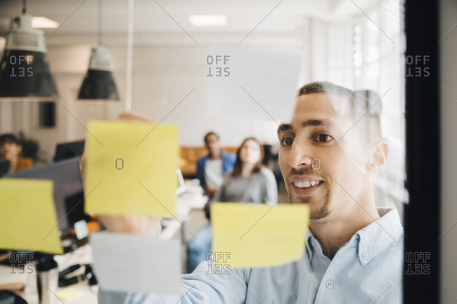 Male computer programmer sticking adhesive note on glass during meeting with colleagues in creative office