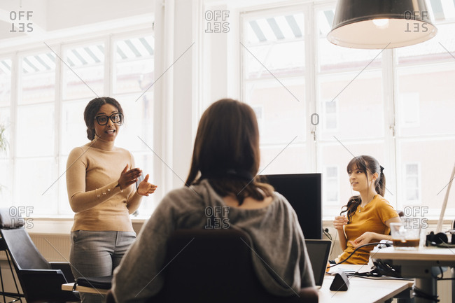 Female computer hackers discussing in creative office