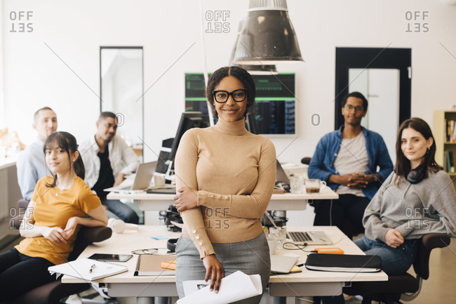 Portrait of smiling businesswoman standing with confident colleagues sitting at desk in creative office