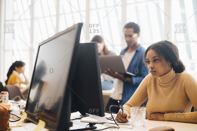 Focused businesswoman using computer while coworkers working in background at office