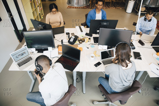 High angle view of IT professionals using technology while sitting at desk in creative office