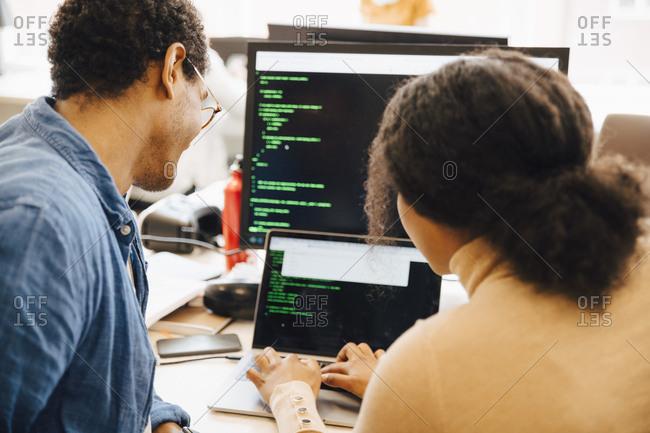 Female computer hacker explaining male coworker over laptop on desk in office