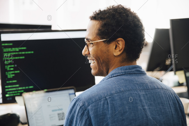Rear view of cheerful male it professional looking away while sitting in creative office