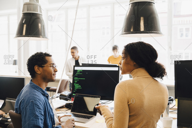 Computer hackers discussing at desk while sitting in creative office