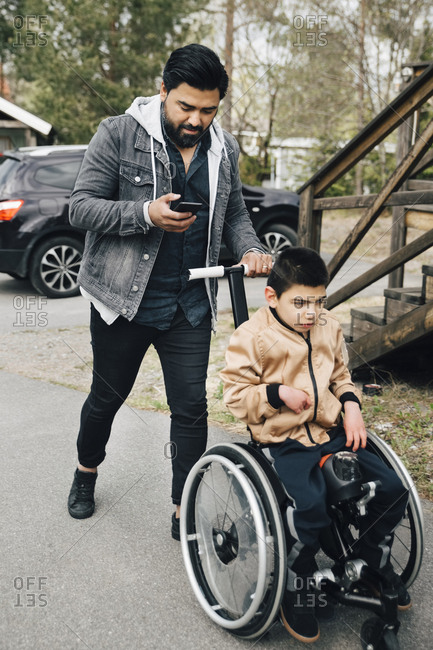 Father using smart phone while pushing autistic son sitting on wheelchair