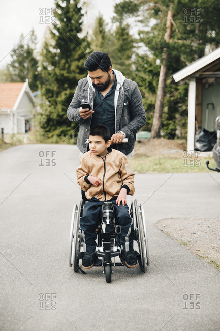 Father using smart phone while pushing autistic son on wheelchair