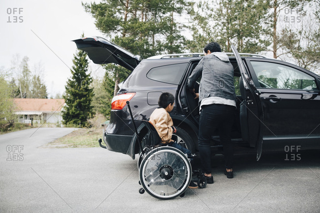 Autistic son waiting by father adjusting car seat on driveway
