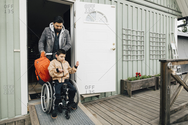 Father with backpack pushing autistic son sitting on wheelchair at doorway