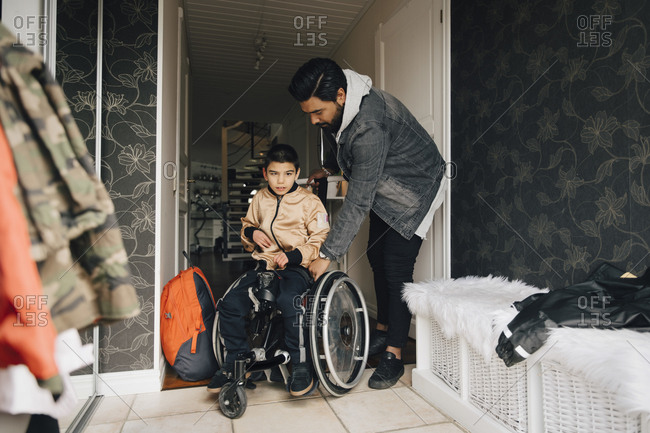 Father pushing autistic son sitting on wheelchair in corridor at home