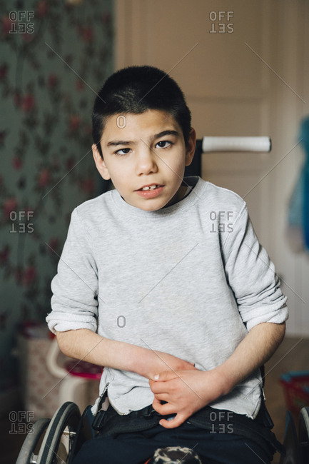 Portrait of disabled boy sitting on wheelchair at home