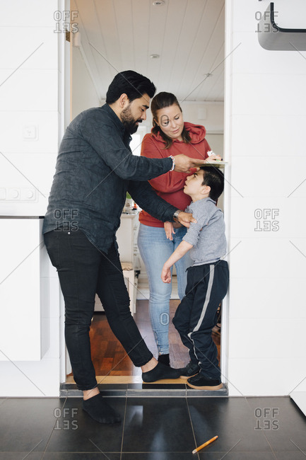 Father and mother measuring height of autistic son by wall at home