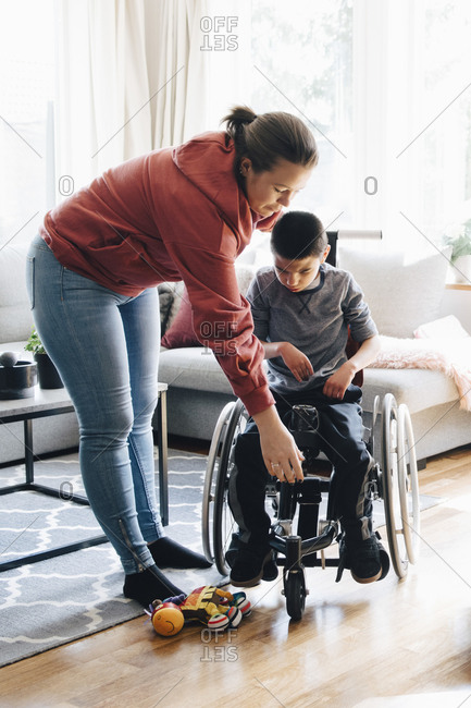 Mother assisting autistic son in sitting on motorized wheelchair at home