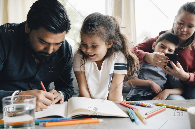 Father teaching drawing to daughter while woman using smart phone with autistic son in background