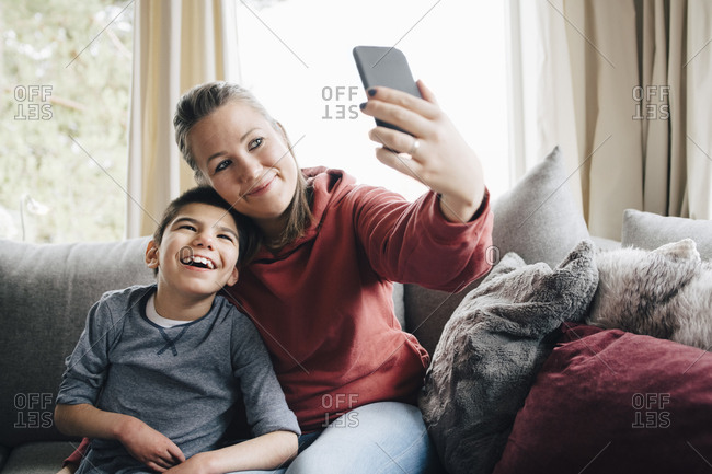 Smiling mother taking selfie with autistic son while sitting on sofa at home