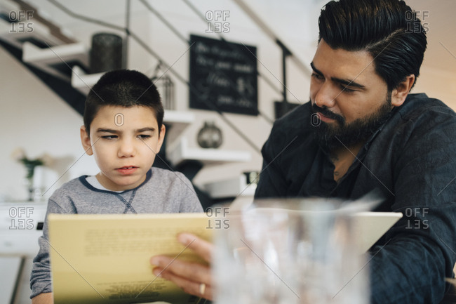 Father teaching autistic son while sitting in living room at home