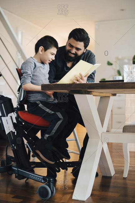 Father teaching autistic son while sitting at table in living room