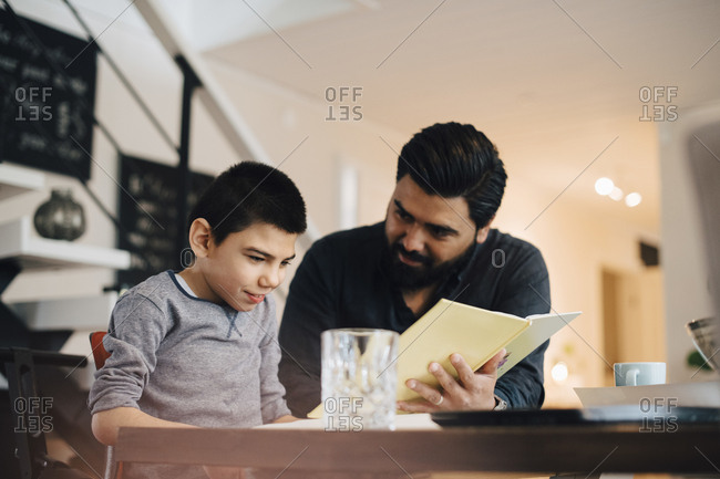 Father teaching autistic son while sitting at table in house