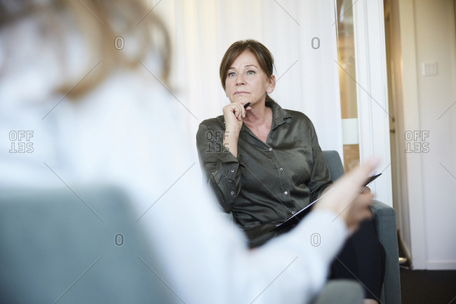 Senior female doctor listening to patient during therapy session