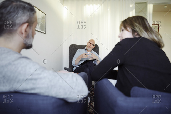 Male therapist explaining couple during therapy session at community center