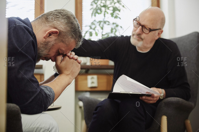 Depressed man crying while therapist consoling him at community center