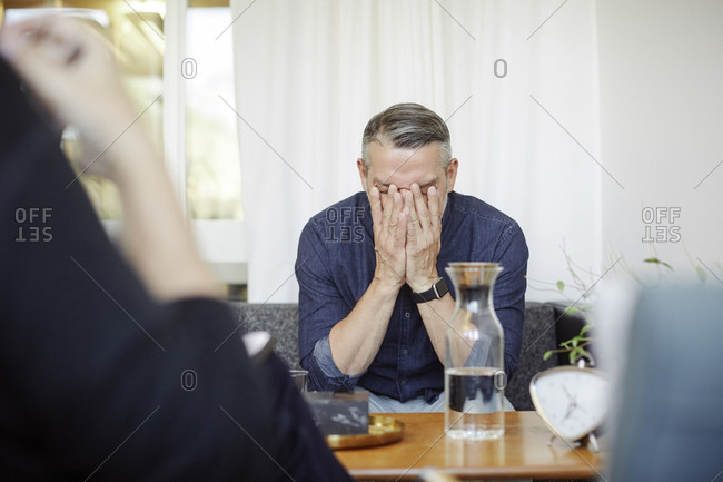 Stressed male patient covering face while sitting with doctor at community center