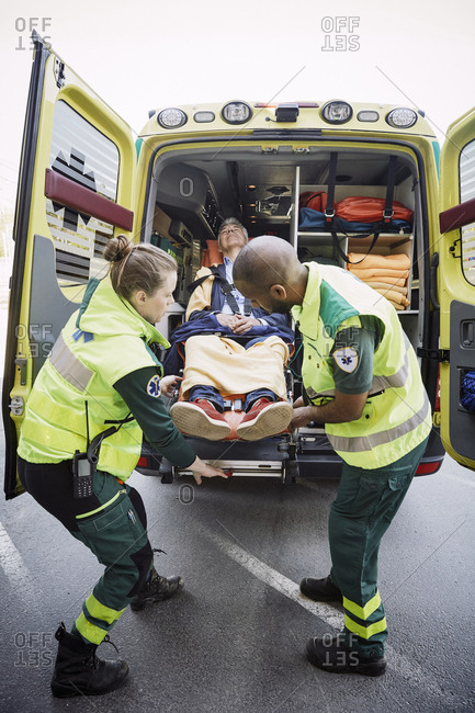 Full length of male and female paramedics unloading patient from ambulance