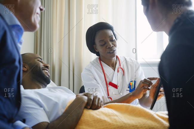 Female doctor explaining medical record over digital tablet to patient and family in hospital ward