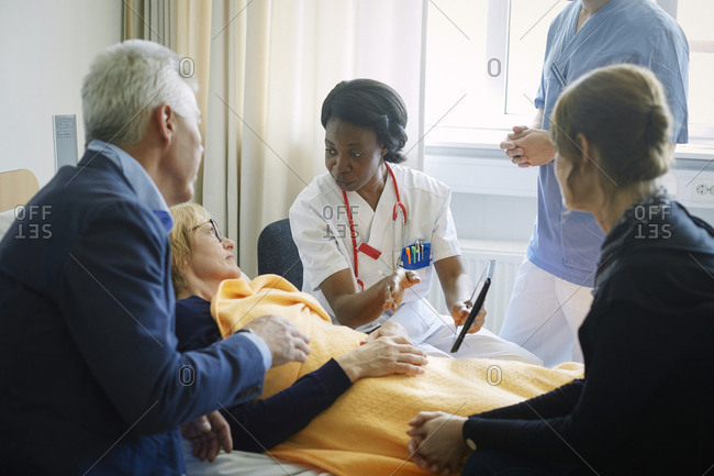 Doctor with nurse explaining mature patient and her friends at hospital ward