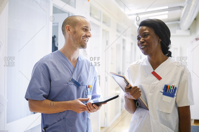 Happy medical professionals in uniform discussing at hospital corridor