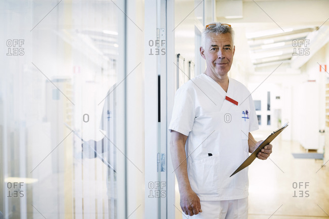 Portrait of confident senior doctor holding clipboard while standing in illuminated corridor at hospital