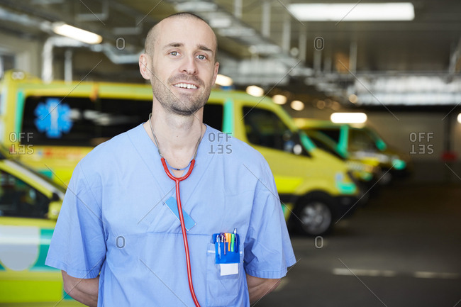 Portrait of smiling male doctor with stethoscope against ambulance in parking lot