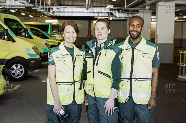 Portrait of confident paramedics standing against ambulance in parking lot