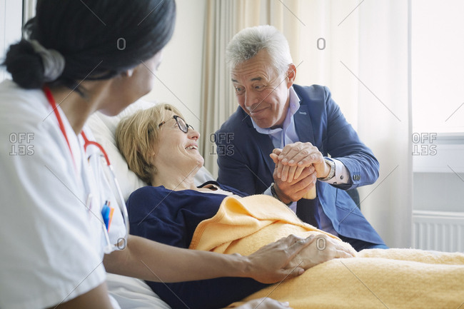 Senior man consoling female patient by doctor in hospital ward