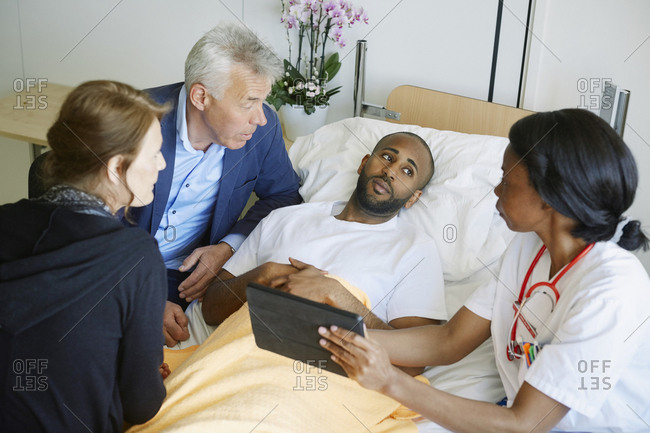 High angle view of doctor discussing over digital tablet with patient and family in hospital ward