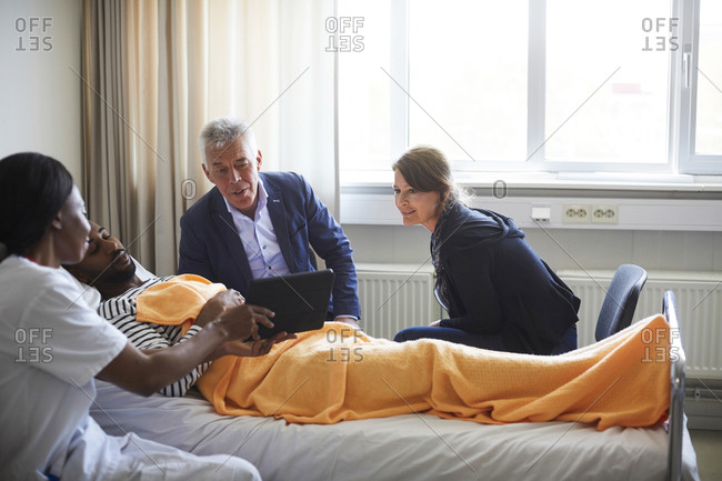 Female doctor showing digital tablet to patient with family in hospital ward