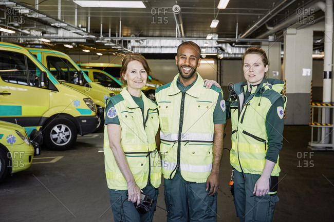 Portrait of male and female ambulance staff standing together in parking lot